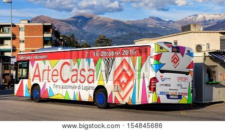 Lugano, Switzerland - 12 October, 2016: a bus at the bus stop on Piazzale Stazione square, mountains in the background. The city of Lugano is the largest city of the Swiss canton of Ticino.