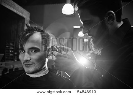 Barber man cutting a client's hair clippers in the barbershop black-white photo