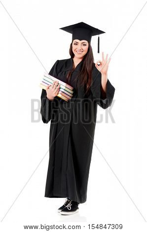 Full length portrait of happy graduation female student holding books and showing ok sign, isolated on white background. Smiling girl in graduation gown looking at camera.