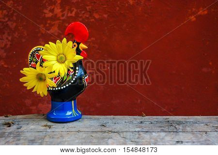 Portuguese rooster with yellow flowers standing on wooden log,with red weathered wall background. Can also be used for new year's cards