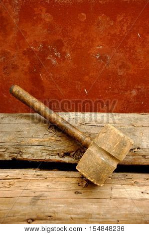 Old Wood Carpenter's Hammer used, standing on wood logs with red weathered wall background, can be a concept or symbol for the end of the work season