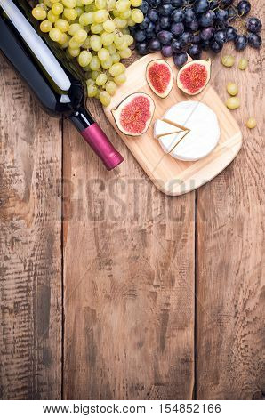 Red Wine, Grapes, Cheese Camambert And Figs On Old Rustic Wooden Table. Food Background. Wine And De