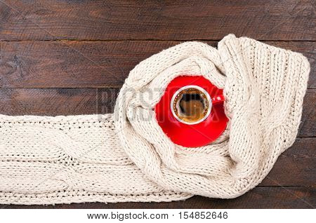 Сoffee Cup And Handmade Knitted Woolen Scarf On Wooden Background. Winter Clothes. Concept Cozy Atmo