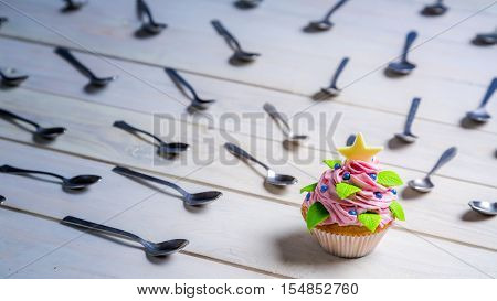 Muffin surrounded by teaspoon on old wooden table