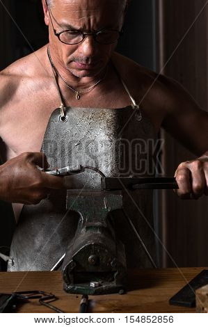 Muscular Middle Aged Artisan working with Metal Vise at his Workshop