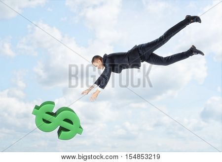 The businessman flying down to the big dollar sign with his hands outstreched on the background of the blue sky. Business and finance. Getting profit. Money problems.