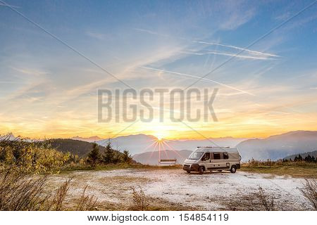 Small Motor Home parked outdoors in the mountains during sunset in autumn.