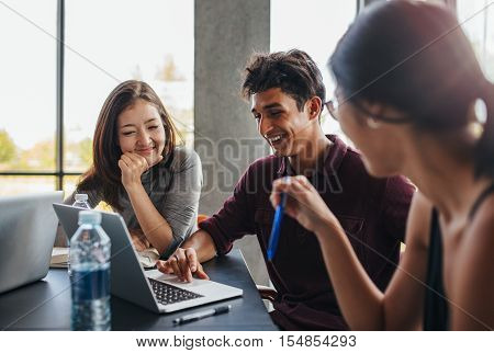 Indoor shot of three young students studying together using laptop. University students smiling and using laptop in college library.