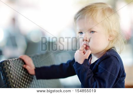 Cute little girl sucking her finger on summer day