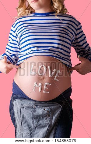Pregnant woman writing 'love me' word on her belly. Trendy Pink background.