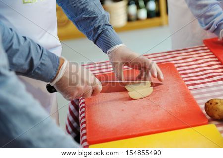 Man hands chopping fresh potato on chopping board