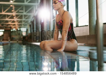 Sporty fit woman relaxing at swimming pool edge. Young woman in swimwear sitting on the edge of pool.