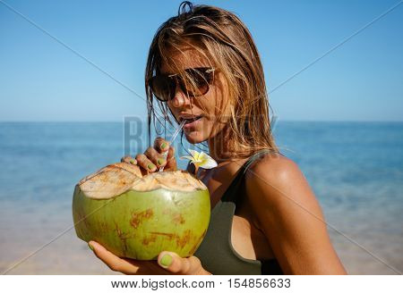 Attractive Woman Drinking Coconut Water On The Beach