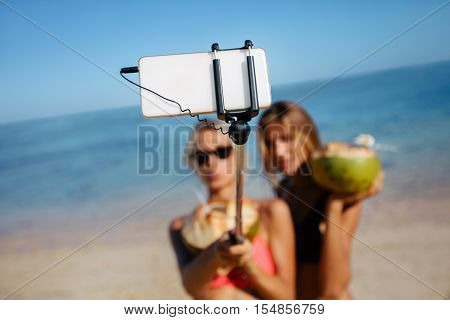Two young female friends taking self portrait with smartphone on the beach. Women on beach holiday taking selfie. Focus on mobile phone attached to selfie stick.