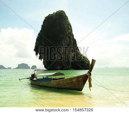 Big wood longtail boat and blue sea under cloudy sky on clif background