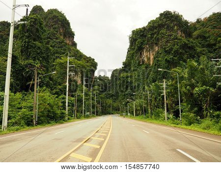 The Car Road in tropical place among big clifs and trees