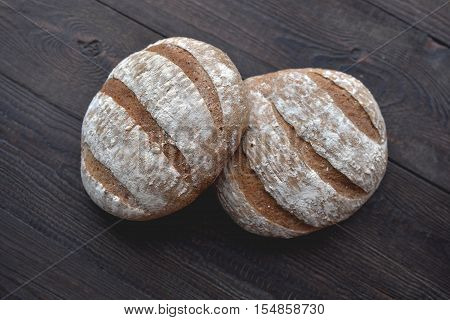 Two healthy hand-made oat breads on a wood table