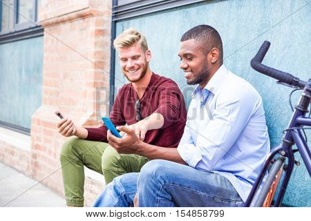 Interracial couple of male friends using phone sitting outside on blue urban wall background - African and caucasian happy men looking down at device screen outdoors - Mobile addiction concept
