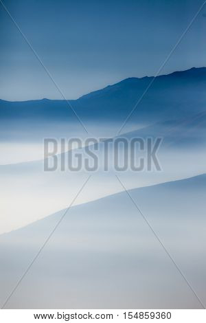 Landscape with colorful layers of mountains and haze in the valleys. Ideal as natural background.