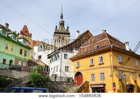 Sighisoara, Romania - October 19th, 2016: View of modern streets with people and cars in historic center of Sighisoara, Transylvania region, Romania
