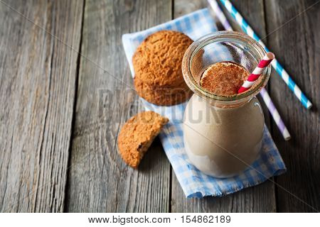 Milk vanilla smoothies with oatmeal cookies in glass jars on the old wooden background. Selective focus.