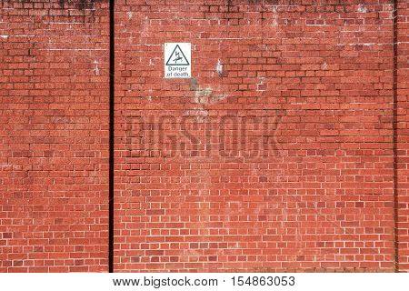 Red Brick Wall With A Warning Sign