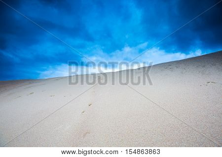 Sand Dunes Under Cloudy Sky At Evening