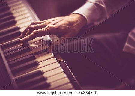 The Piano Player. Male Hand on the Piano Closeup Photo.