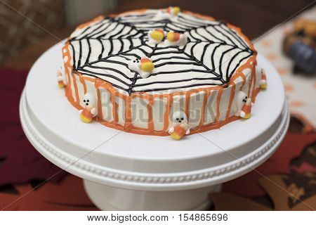 White frosting Hallowen cake with orange and black icing and candy ghosts