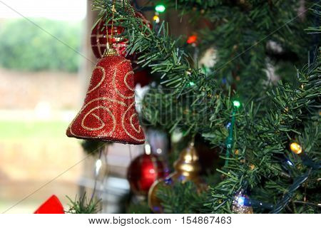 A red bell with gold striped patterns hanging from a Christmas tree