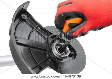 Photos hands working with screwdriver mounting protective cover on the new weed trimmer isolated on white background with clipping paths