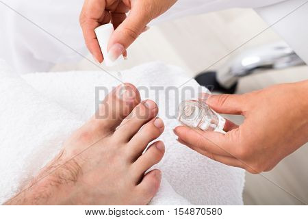Close-up Of A Manicurist Applying Moisturizing Nail Oil On Person's Toenail