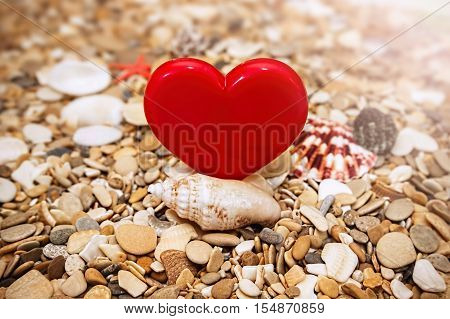 Red heart on a beach background. The pebbles sea shells and starfish.