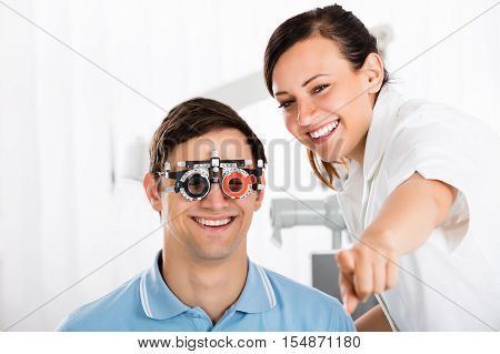 Young Smiling Female Optometrist Examining Patient's Vision With Trial Frame