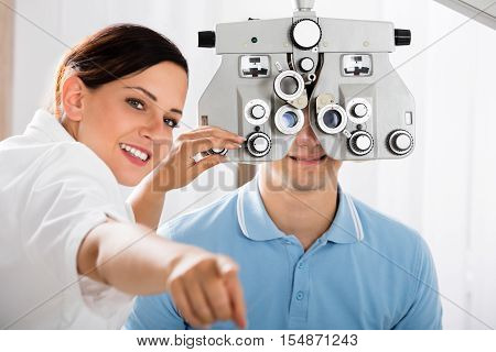 Happy Female Optometrist Doing Sight Testing For Male Patient In Clinic