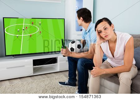 Sad Woman Sitting Beside A Man Busy Watching Sports On Television At Home