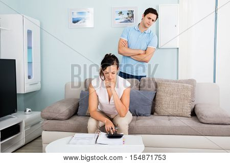 Suspicious Man Looking At His Wife Busy Calculating Bills On Sofa At Living Room