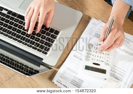 Hands Using Pen, Calculator And Computer For Accounts