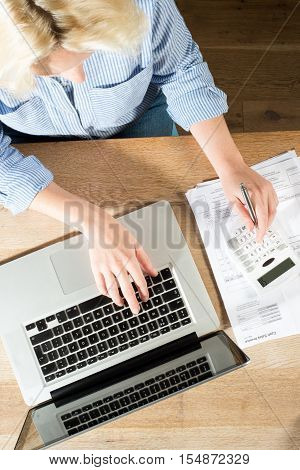 Overhead shot of blonde woman in striped blue shirt holding a pen and using a laptop printed papers and calculator to do accounts or bookeeping at a wooden desk