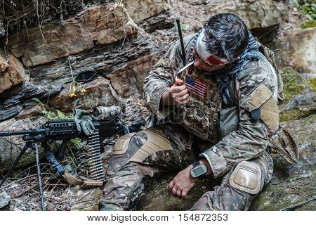 Wounded army ranger machine gunner in the mountains