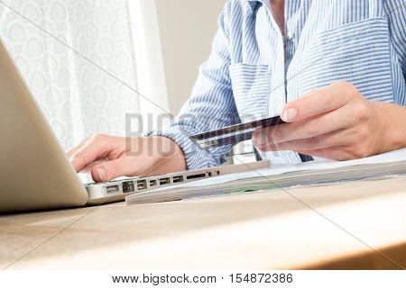 Hands Holding Credit Or Debit Card Using Computer At Desk