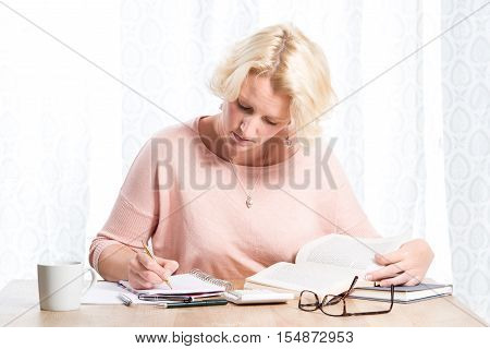 Woman Writing On Paper While Reading From Books