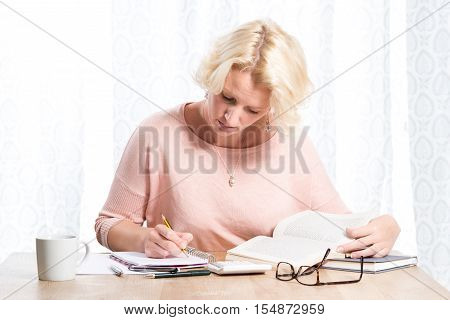 Sitting Woman Writing On Paper While Reading From Books