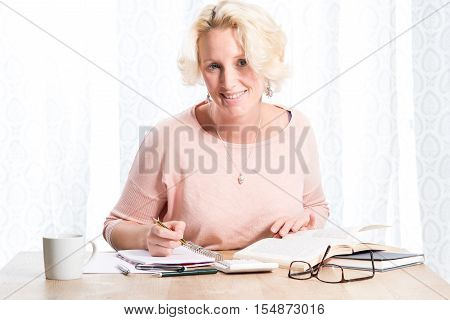 Woman Smiles While Reading And Writing At Wooden Desk