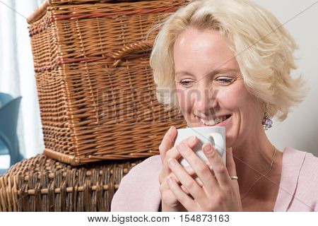 Blond Woman With Hot Drink Smiles To Herself
