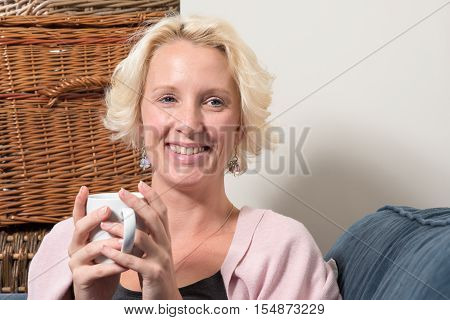 Blonde Woman On Couch With Hot Drink Smiles Copy Space