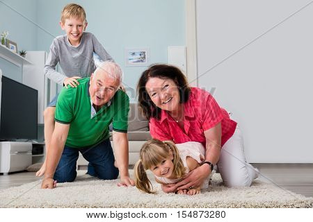 Happy Grandparents And Grandchildren Playing And Cuddling While Lying On Carpet In Living Room