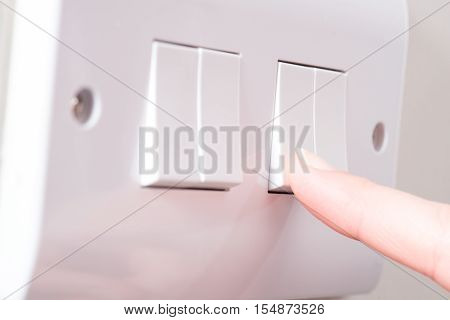 Finger Pressing Light Switch On A 4 Gang Switch Plate