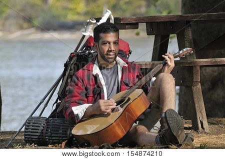 Happy traveling man playing acoustic guitar out near a picnic bench