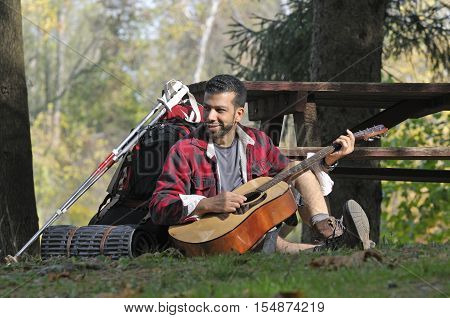 Hispanic tourist playing guitar outside on a forest campsite
